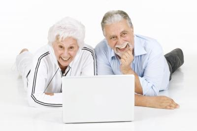 Boomer couple using a laptop together on the floor